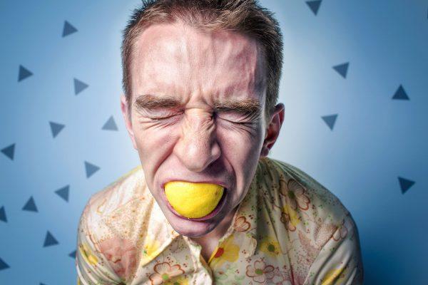 Un uomo stressato che morde un limone